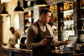 Smiling bartender at cash register working in a pub.