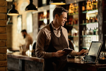 Happy waiter working at cash register in a bar.