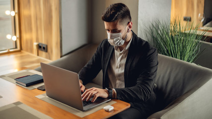 Caucasian adult bearded man indoors in cafe. Lifestyle concept photo with copy space. Picture with handsome guy who using protective face mask. Portrait with gray laptop Papier Peint