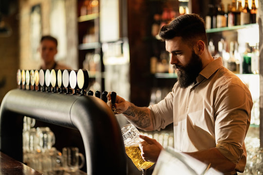 Young bartender pouring beer from beer tap while working in a pub.