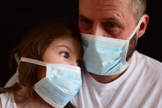 Man and child in medical masks.