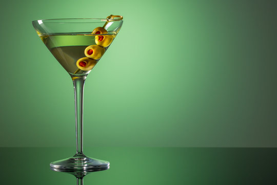 Glass of Martini with olives. Extra dry vermouth martini. Alcohol cocktail on green background. Copy space.