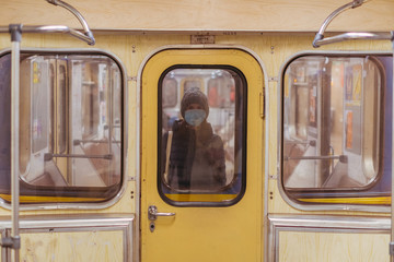 Woman in medical mask traveling in subway train