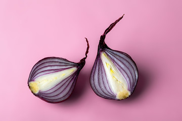 Two halves of fresh purple onion on a pink background. Red ripe onion against purple. Organic vegetables and fruits. Veganism and raw food diet.