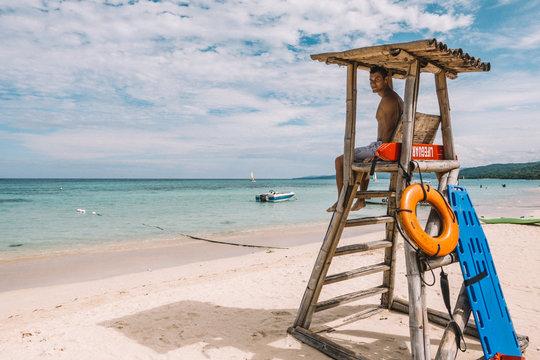 Man Sitting On Lifeguard Chair On Beach Against Sky
