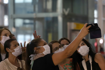 Women wearing protective face masks takes pictures at international arrivals area at Guarulhos International Airport in Guarulhos