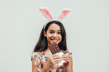 Portrait of happy little girl celebrating easter eating chocolate