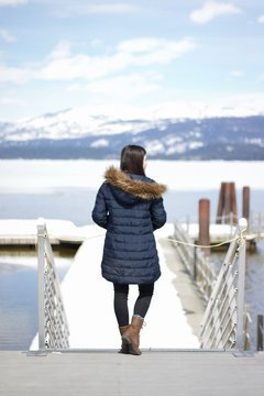 Rear View Of Woman Wearing Warm Clothing Standing On Pier Over Sea