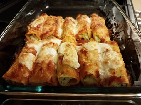 hot baked stuffed manicotti pasta in glass bowl on stove