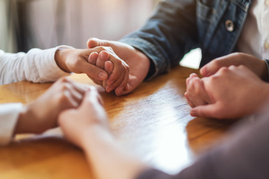 Group of people sitting in a circle holding hands and pray together or in therapy session