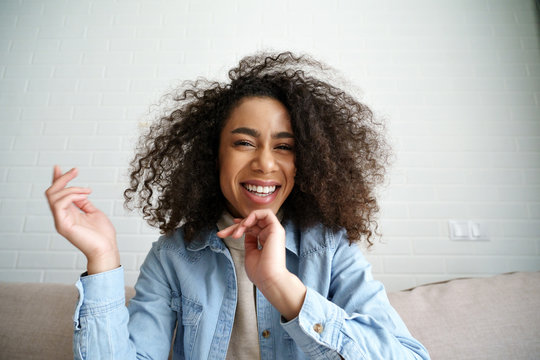 Cheerful african teenage girl blogger talking to camera recording vlog. Happy mixed race young woman laughing making video call at home. Funny social media influencer streaming blog. Webcam view.