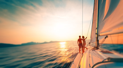Young couple enjoys sailing in the tropical sea at sunset on their yacht. Motion blurred image