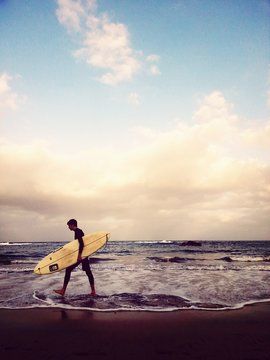 Side View Of Man Carrying Surfboard On Sea Shore