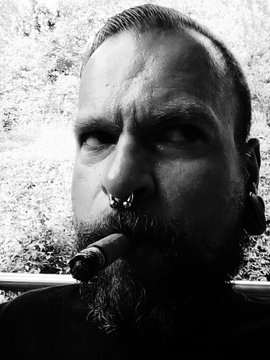 Close-up Of Mid Adult Man Smoking Cigar With Pierced Nose