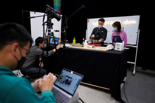 Chefs wearing face masks conduct a cooking lesson through a live-streaming session inside a restaurant at a office as the country is hit by an outbreak of the novel coronavirus that can cause COVID-19 disease, in Shanghai