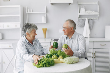Couple in a kitchen. Grandparents sitting at home. Woman with vegetables