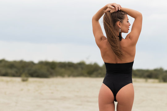 Sensual slim female in black swimsuit on beach
