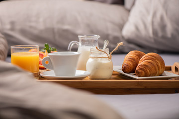 Breakfast in bed with  orange fruits and pastries on a tray