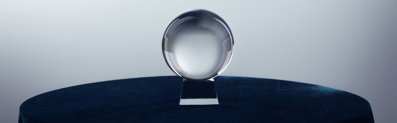 Crystal ball on round table on grey background, panoramic shot