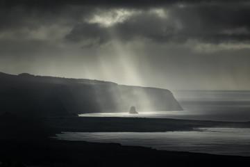 Darkness over islet boulder in the coastline