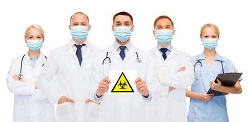 health, medicine and pandemic concept - doctors wearing protective medical masks holding biohazard...