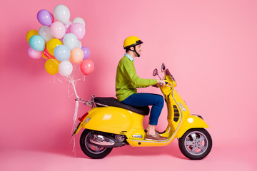 Profile side view of his he nice attractive cheerful cheery glad guy driving moped bringing carrying bunch air balls festive decoration isolated over pink pastel color background