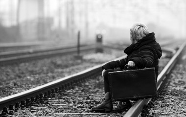 Side View Of Woman With Suitcase Sitting On Railroad Track