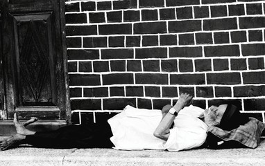 Senior Man Sleeping On Footpath Against Brick Wall
