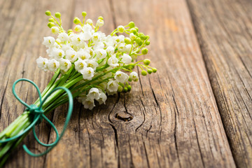 Wall Murals Lily of the valley bunch of lily of the valley flowers on old weathered wooden table