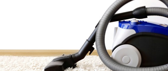 Canister modern vacuum cleaner blue for cleaning the house on the background of the wall and soft carpet. Equipment, room cleaning,vacuuming. Banner with Copy space for text.