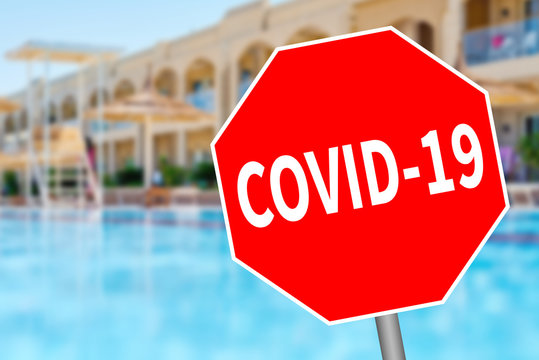 Impact of coronavirus on tourism industry and beach holidays. Quarantine and control of tourists infected with coronavirus. Hotel with swimming pool and inscription COVID-19 on prohibition sign