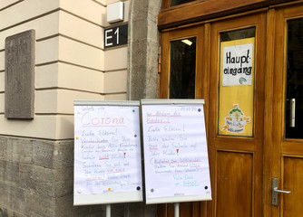Two boards advising parents to drop off and pick up their children outside the building are placed in front of the Brueder Grimm school in Berlin