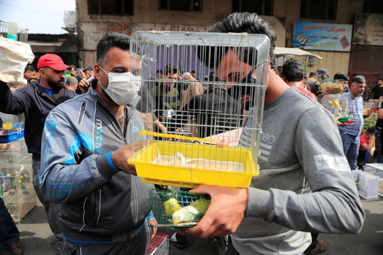 Iraqi men wearing protective masks, following the outbreak of coronavirus, as they sell animals at the Ghazal pet market in Baghdad