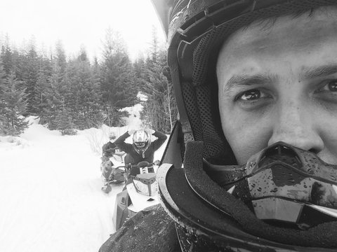 Close-up Portrait Of Man Riding Snowmobile On Field With Friends In Background