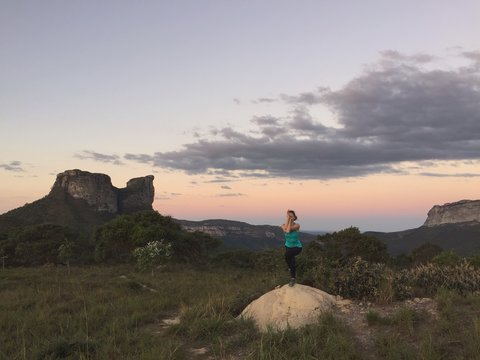 Full Length Of Woman Doing Yoga On Rock Against Sky During Sunset At Chapada Diamantina National Park