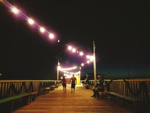 Rear View Of Couple Walking On Boardwalk In South Padre Island At Night