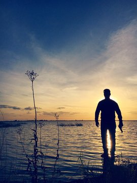 Silhouette Man With Gun Standing On Rock In Lake Against Sky During Sunset