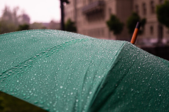 Close up view of a green umbrella with rain droplets and out of focus building in the background