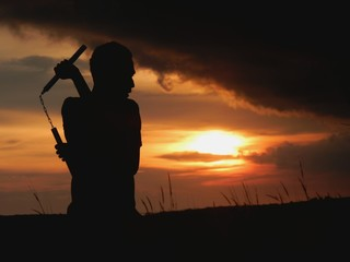 Silhouette Man Practicing Martial Arts With Nunchaku During Sunset