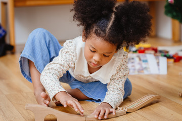 little cute child girl enjoy playing wood puzzle on the wooden floor at home in living room.