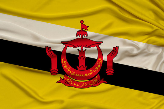 national flag of the state of Brunei on delicate shiny silk, concept of the country's population, unity, horizontal, close-up, copy space