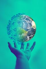 Fototapeta Coronavirus globalna pandemia. Ręka człowieka chwyta ziemię zarażoną epidemią. Pionowy transparent przeciwdziałanie broni biologicznej.  obraz