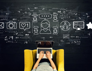Wall Mural - Social media theme with person using a laptop in a chair