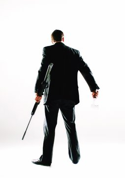 Rear View Of Mature Man Holding Gun While Standing Over White Background
