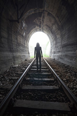 Rear View Of Woman Standing On Railroad Track In Tunnel