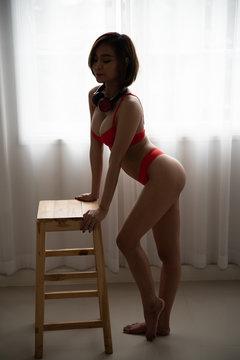 Asian young woman wearing bikini with headphones in bedroom.