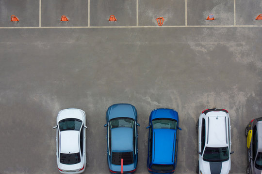 Car parking aerial top view. Occupied and vacant lots with vehicles. Park marked area of modern urban structure. City landscape pattern