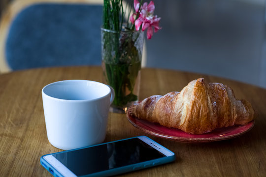 Breakfast in coffee shop. Cup of coffee and fresh croissant in plate. Flowers in glass.