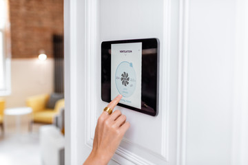 Fototapeta Controlling home ventilation or conditioning with a digital touch screen panel. Concept of wireless ventilation control and smart home obraz