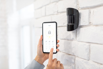 Obraz Controlling alarm system with smart phone and special mobile application wireless, holding device the motion sensor indoors - fototapety do salonu